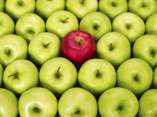 Image of a group of green apples with one red apple meant to depict how native advertising conceptually fits within the context of a website