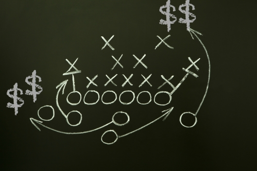 Image of a football play with dollar signs shown along receiver routes. The image is meant to depict the opportunities for marketers to capitalize on the excitement and increased number of games that are a part of the new College Football Playoff system