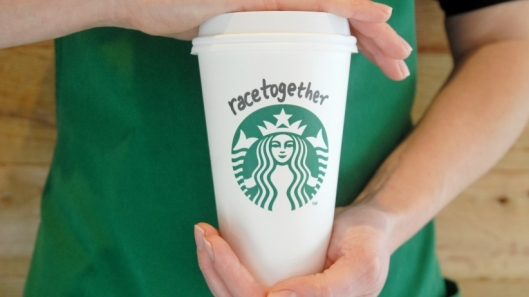 """A Starbucks barista holds a Starbucks cup with """"Race together"""" written on it."""