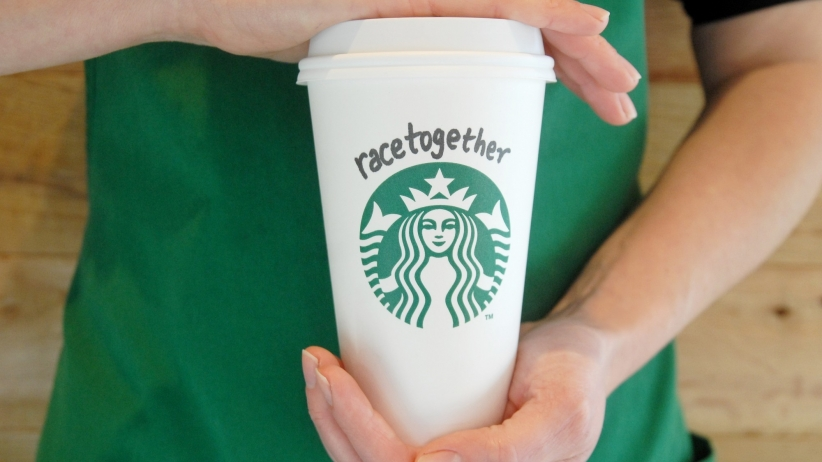 "A Starbucks barista holds a Starbucks cup with ""Race together"" written on it."