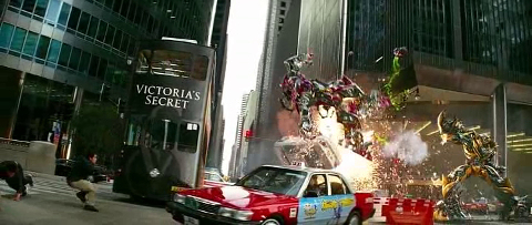 "Transformers battle on the street as a double decker bus with ""Victoria's Secret"" written on the front approaches."