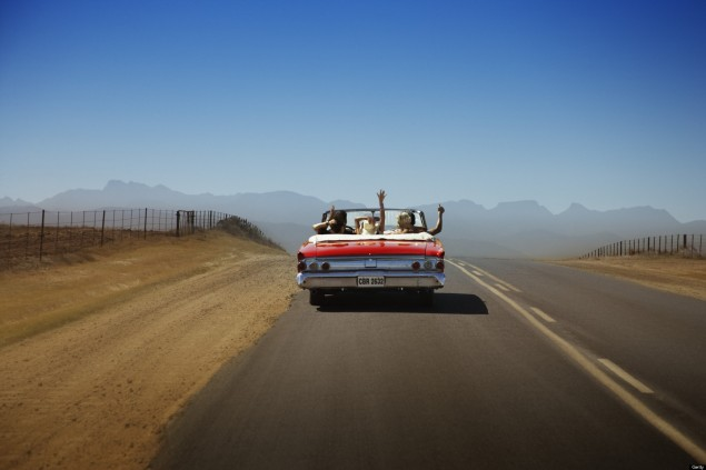 A car with three celebratory passengers in it drives off into the desert during a road trip.