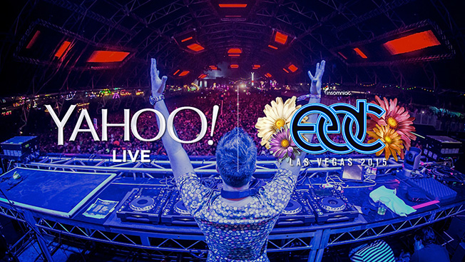 A DJ standing behind a DJ booth during a festival with the sponsor Yahoo! and EDC Las Vegas written on top of him.