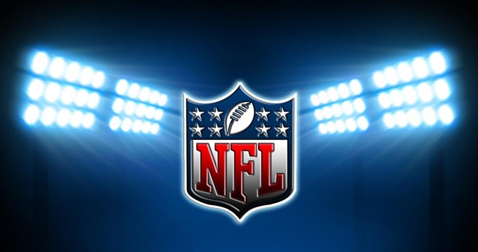 The NFL logo under football stadium lights.