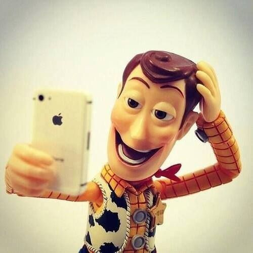 A plastic Woody doll, a character from Toy Story, taking a picture of himself with an iPhone.