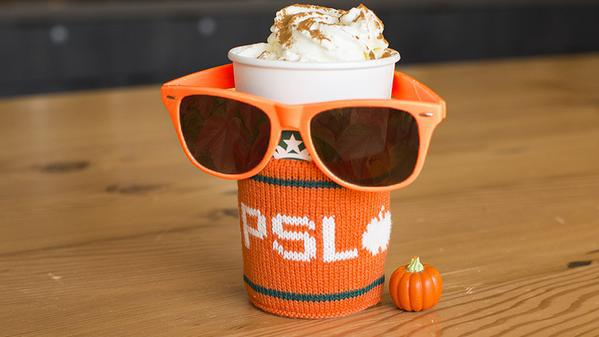 A to-go coffee cup from Starbucks with a PSL knit sleeve, a pair of orange sunglasses, and a small plastic pumpkin.
