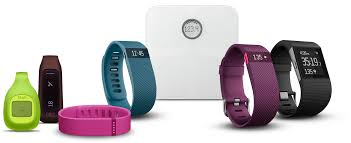 Several types of FitBit (fitness activity tracker) devices, such as a watch and a belt clip, lined up.
