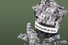 "A trashcan filled with $100 bills with a label on the can saying ""marketing dollars go here."""