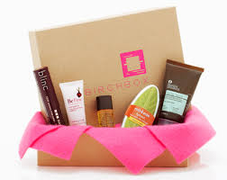 A brown birchbox with pink lettering and several types of makeup surroudning the box.