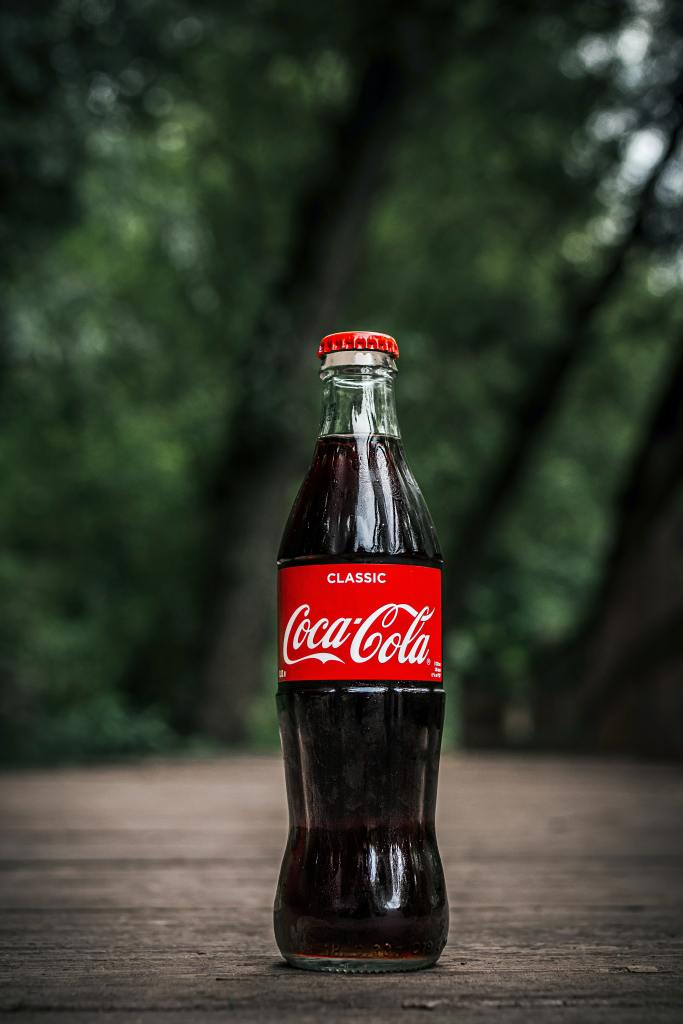 A close up of a glass Coca-Cola bottle