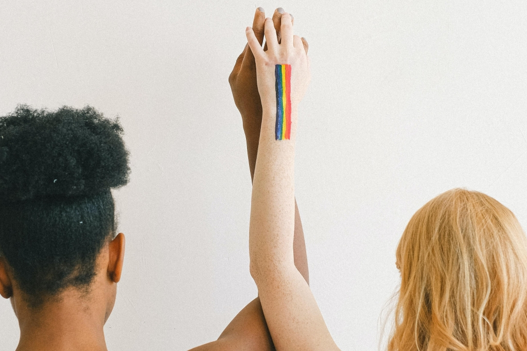 Two women holding hands, one with a rainbow pride flag painted on her arm